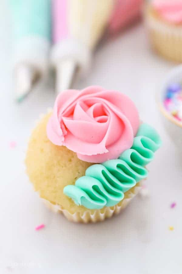 A vanilla cupcake with a pink rose and green ribbon of frosting
