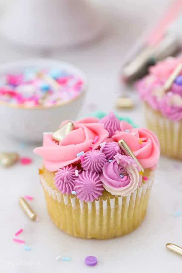 A unicorn inspired cupcake is covered with purple, pink and green frosting swirls and gold sprinkles