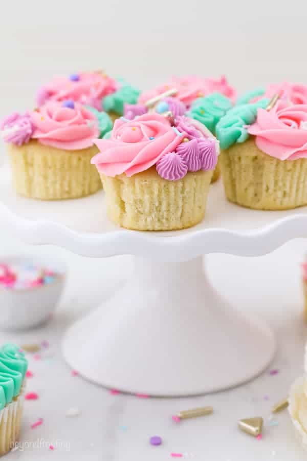 A white cake stand filled with gorgeous buttercream frosted Unicorncupcakes