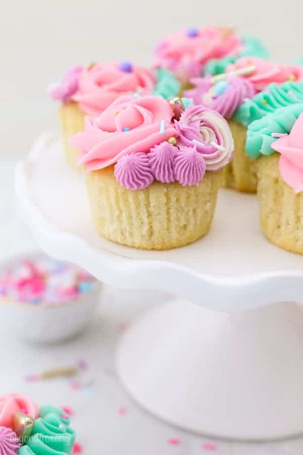 a close up of an unwrapped vanilla cupcake with gorgeous, colorful buttercream swirls