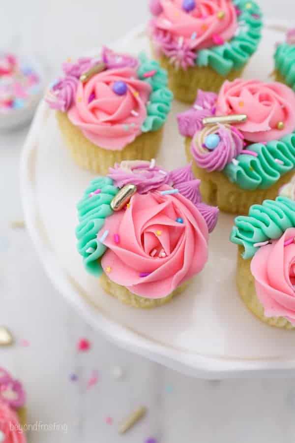 Colorfully frosted cupcakes on a white cake plate