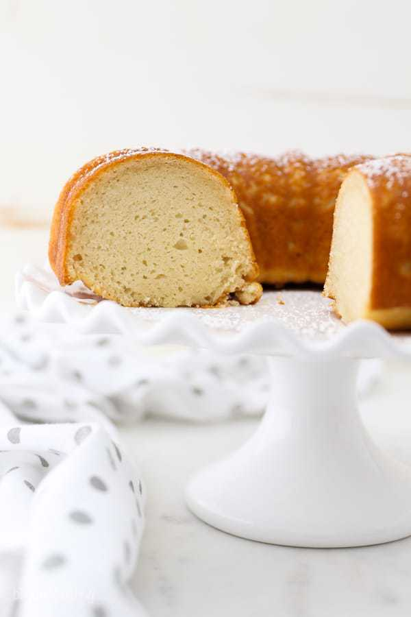 A peek inside a sliced vanilla bundt cake on a white ruffled edge cake stand