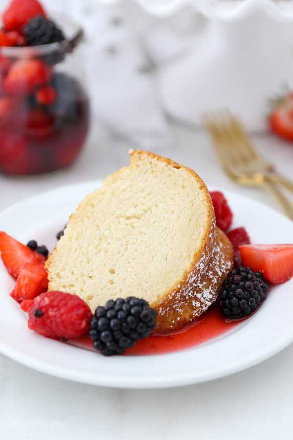 A gorgeous slice of vanilla bundt cake on a white plate surrounded by fresh berries in juices