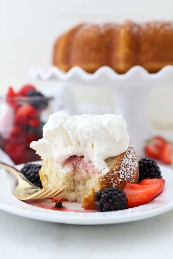 A slice of vanilla cake drizzled with berries and juice and topped with whipped cream, a gold fork is laying on the plate