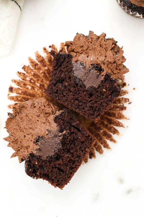 Laying on it's side, a chocolate cupcake with a chocolate ganache filling is cut in half to show the filling on the inside of the cupcake