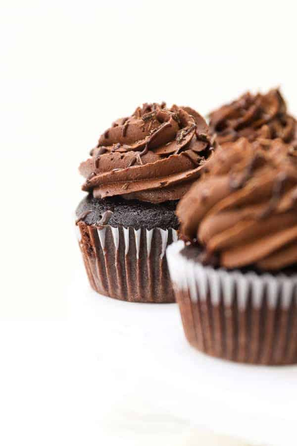 A gorgeous shot of a chocolate cupcake with a swirl of frosting, drizzled with chocolate