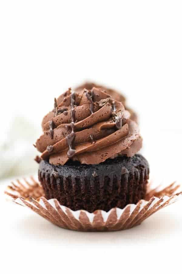 A chocolate cupcake with the wrapper pulled back is frosted with a tall swirl of chocolate frosting and drizzled with ganache