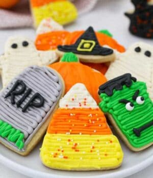 A plate of gorgeous decorated halloween sugar cookies with candy corns, pumpkins, Frankensteins, and tombstones