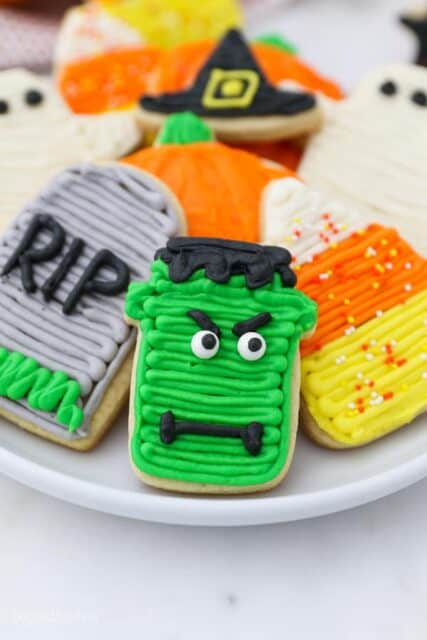 A Frankenstein decorated sugar cookie with green frosting, eyes and a mouth on a plate with other halloween cookies