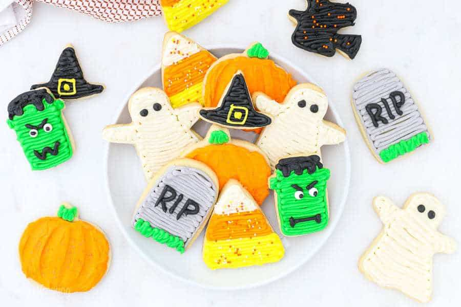 An overhead shot of plate of gorgeous decorated halloween sugar cookies with candy corns, pumpkins, Frankensteins, tombstones, ghosts and witches hats.