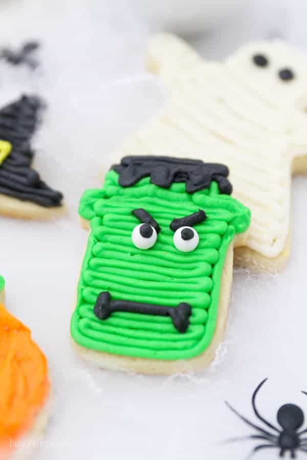 A Frankenstein decorated sugar cookie with green frosting, eyes and a mouth