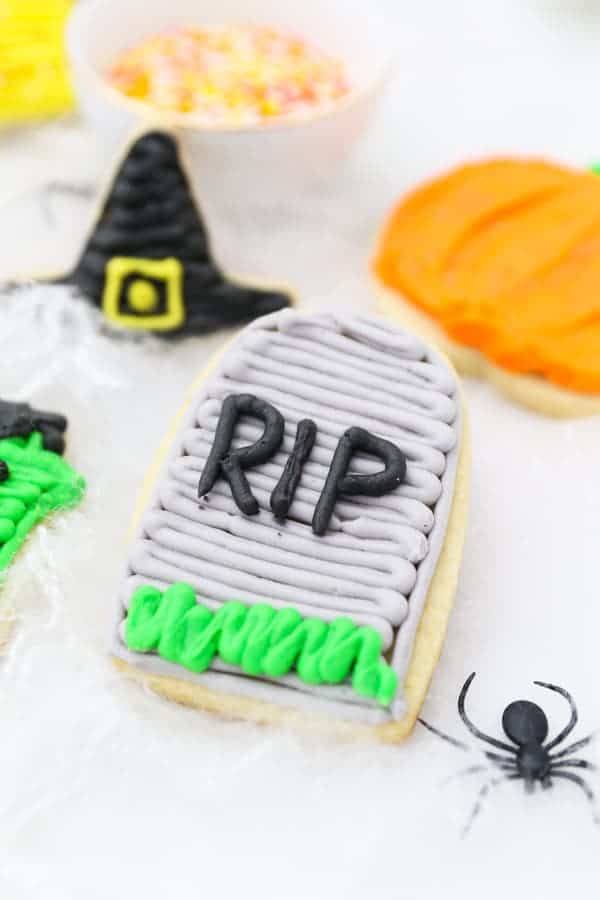 An RIP tombstone sugar cookie laying in fake spider webs