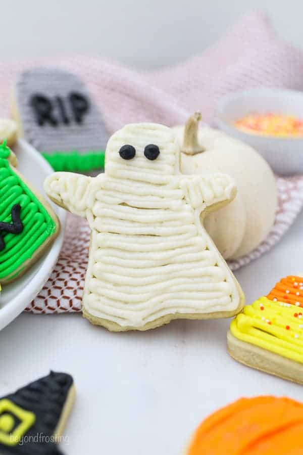 A ghost cookie decorated with buttercream is leaning against a mini white pumpkin