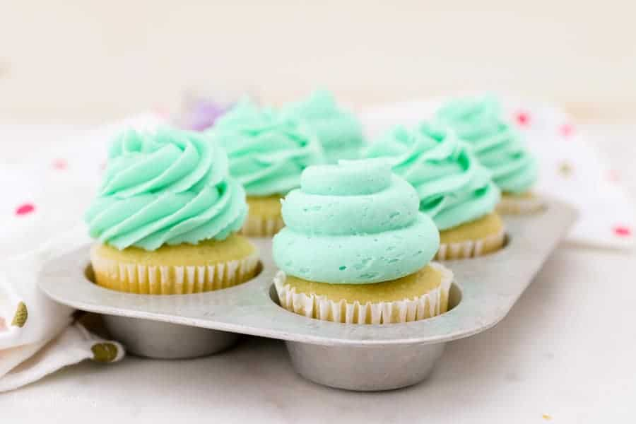 A vintage baking tray with 6 decorated cupcakes with teal frosting