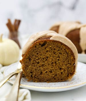 A slice of moist pumpkin cake with a glaze, and two gold forks hanging off the white plate