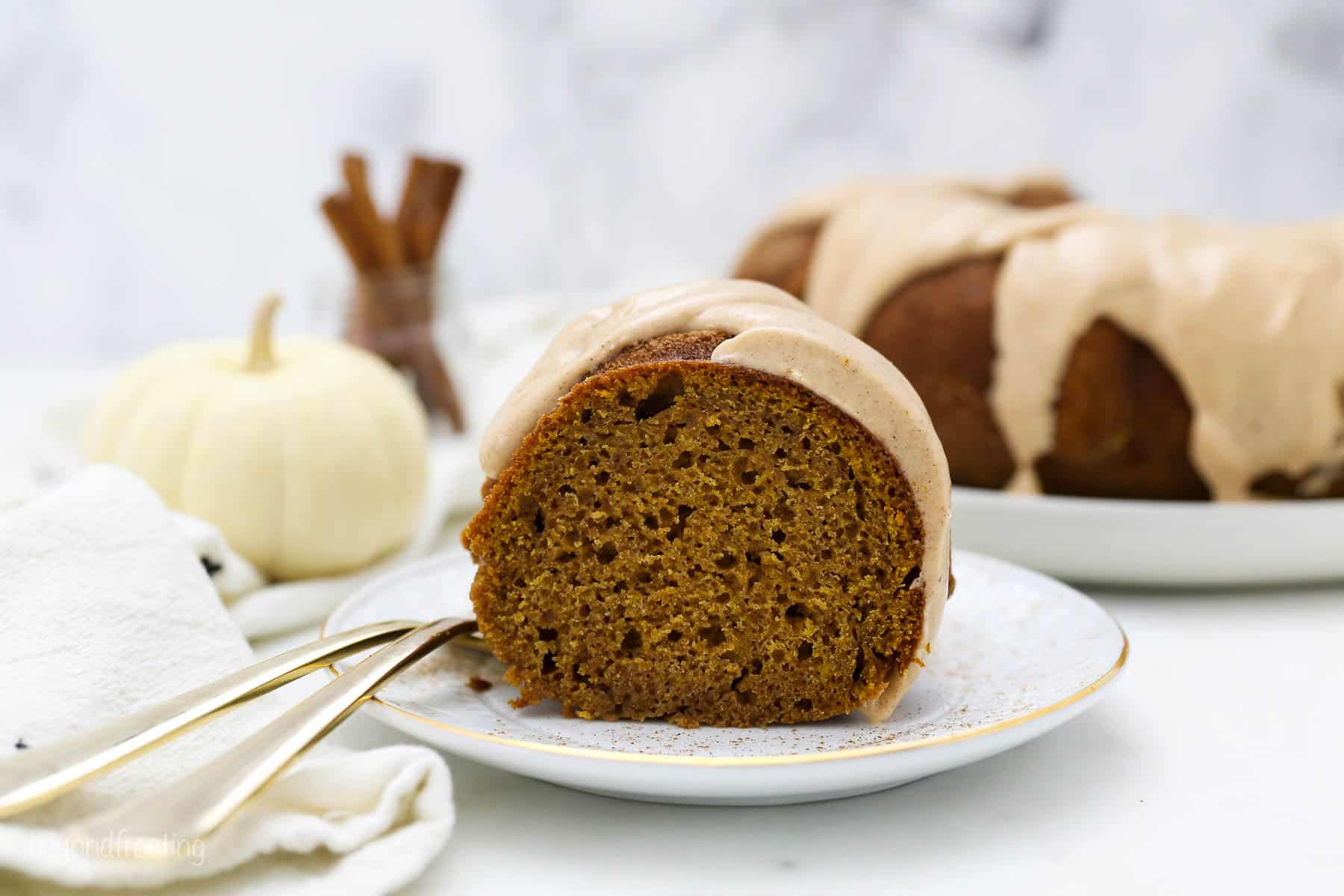 A wide angle shot of a slice of moist pumpkin cake with a glaze, and two gold forks hanging off the white plate