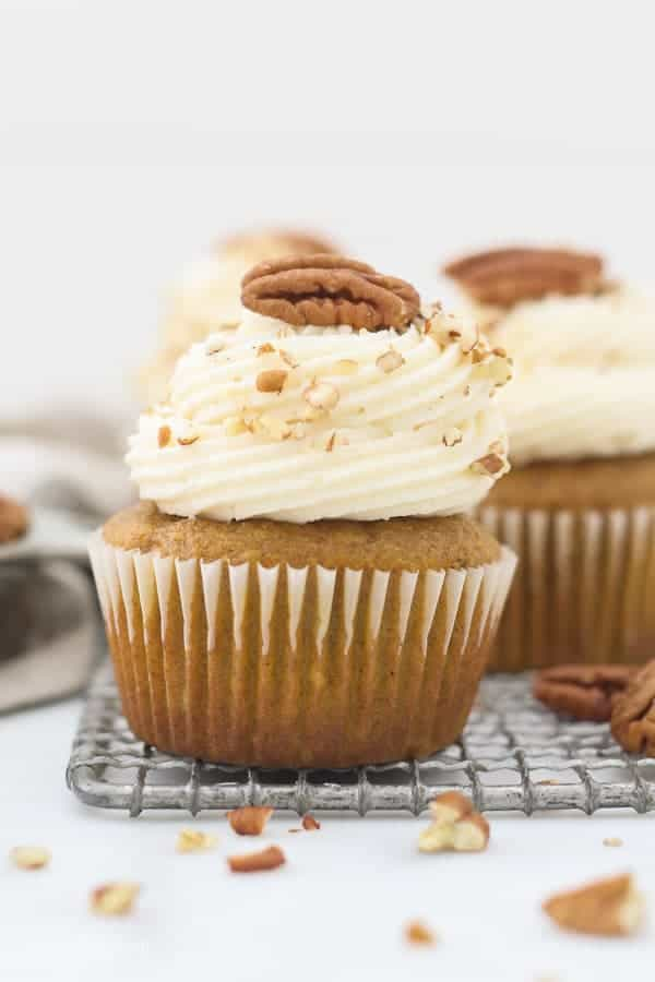 A vintage wire baking rack with a couple pumpkin cupcakes with a gorgeous frosting swirl and pecans on top