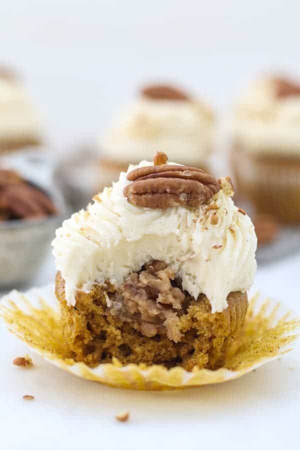 A pumpkin cupcake with a big bite out of it showing the center of the cupcake filled with a pecan pie filling and it's topped with a beautiful frosting.
