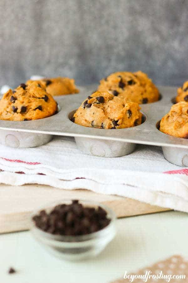 A vintage cupcake tray with sweet potato muffins and a little dish of chocolate chips on the side