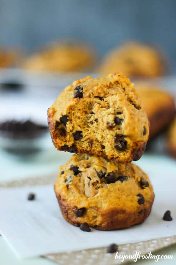 Two stacked muffins, the top one has a big bite missing