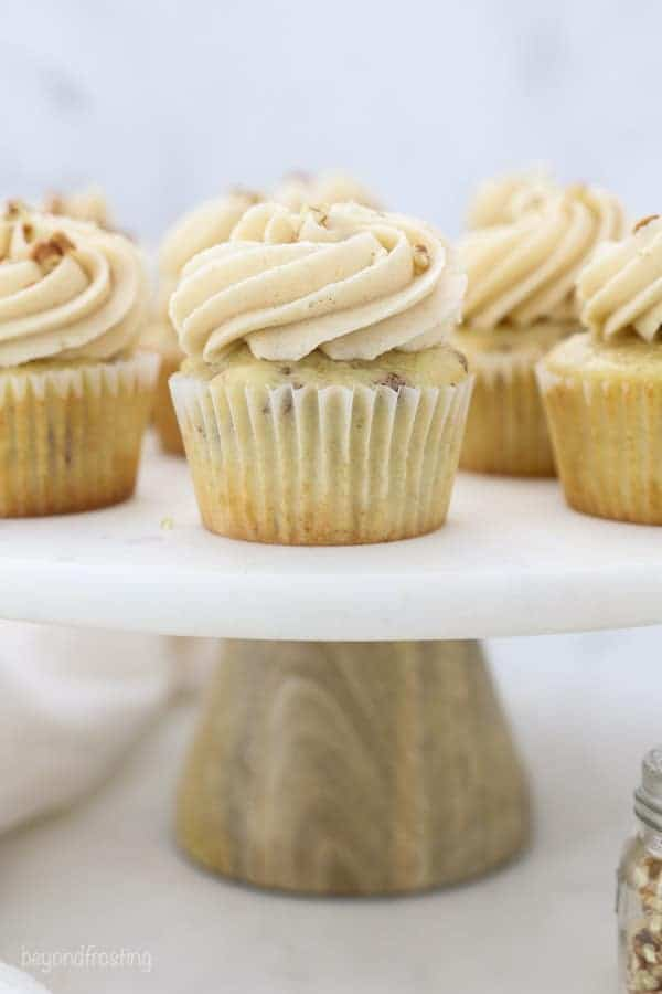 A marble cake stand with a wooden base is topped with pecan cupcakes