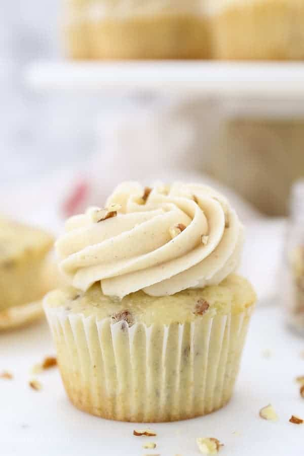 A close up of vanilla cupcake, frosted and topped with pecans