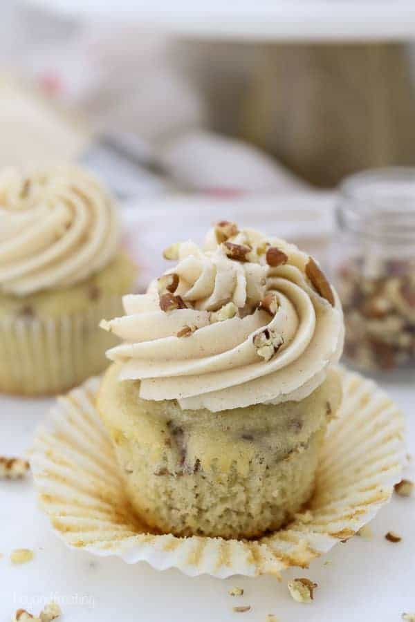 A cupcake, unwrapped showing the pecans inside, and the frosting swirl is covered with chopped pecans