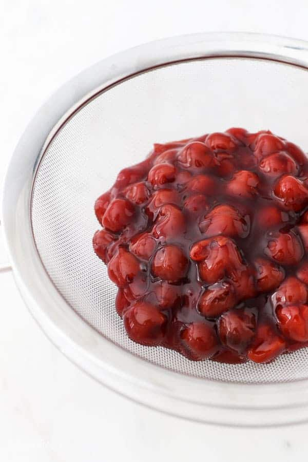 Cherry pie filling in a strainer