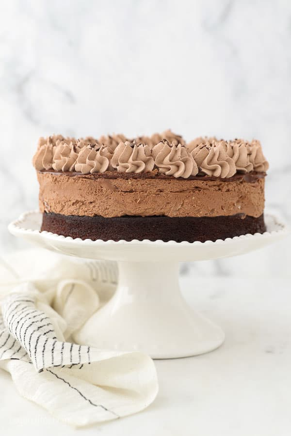 A white ruffled cake stand with a chocolate mousse cake