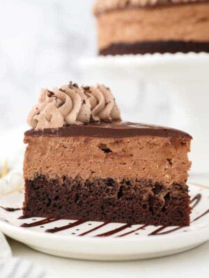 A close up shot showing the layers of the chocolate mousse cake. A layer of chocolate cake and a thick chocolate mousse is covered with ganahce.