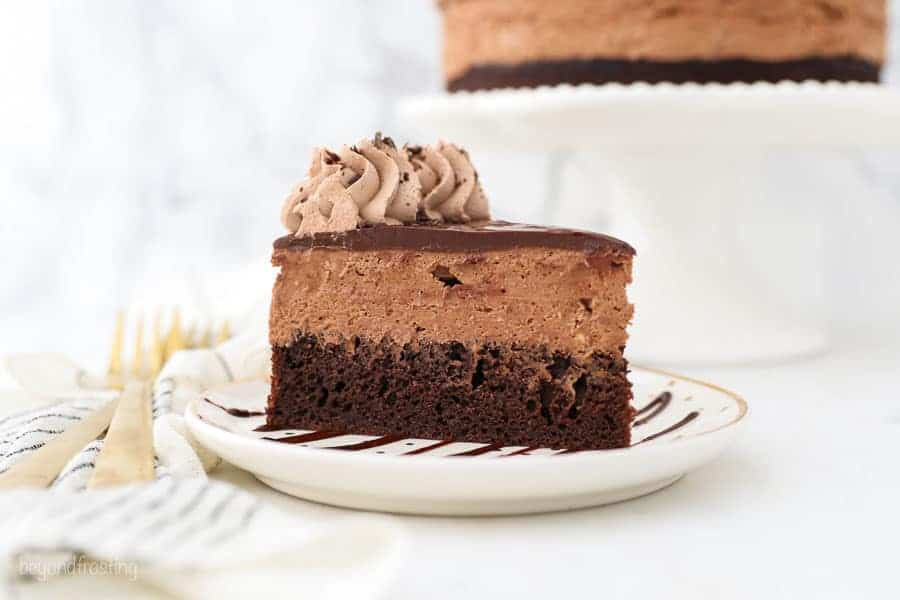 A horizontal image of gorgeous slice of chocolate mousse cake on a gold polka dot cake