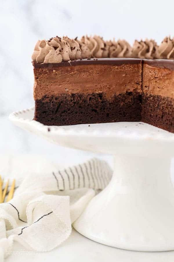 A double layer chocolate mousse cake, with slices missing showing the inside of the cake