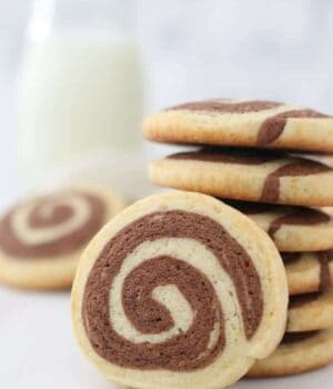 A gorgeous pinwheel cookie leaning up against another stack of cookies