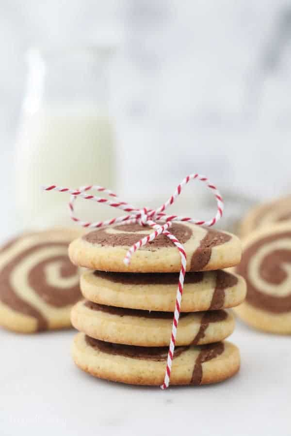 A stack of pinwheel cookies with a red and white ribbon bakers twine tied around them