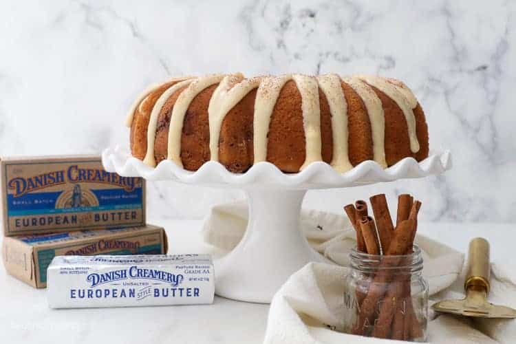 A wide photo of a white ruffled cake stand with a bundt cake covered with glaze, and 3 packages of danish creamery butter sitting next to it