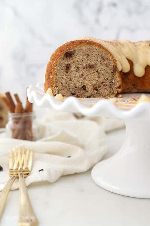 A white ruffled cake stand with a bundt cake on it that been sliced, showing you the inside of the bundt cake