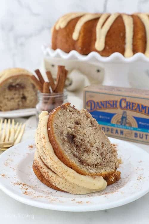 A slice of cinnamon bundt cake on a round plate with a package of Danish Creamery butter in the background