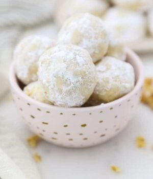A small pink dish with gold polka dots is filled with Mexican Wedding Cookies