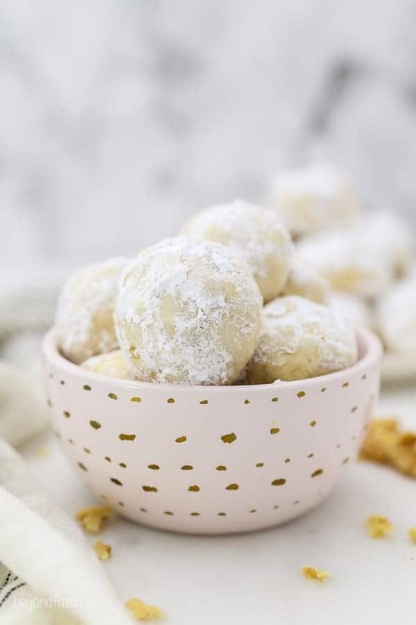 A small pink dish with gold polka dots is filled with Snowball Cookies