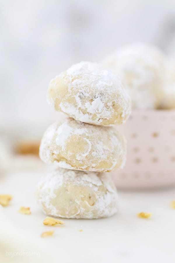 A stack of 3 Snowball Cookies rolled in powdered sugar
