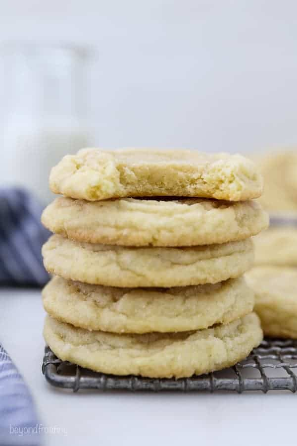 A stack of easy sugar cookies and the cookie on top has a bite taken out it