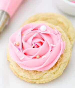 A gorgeous sugar cookie decorated with a 1M pink rose with gorgeous sprinkles