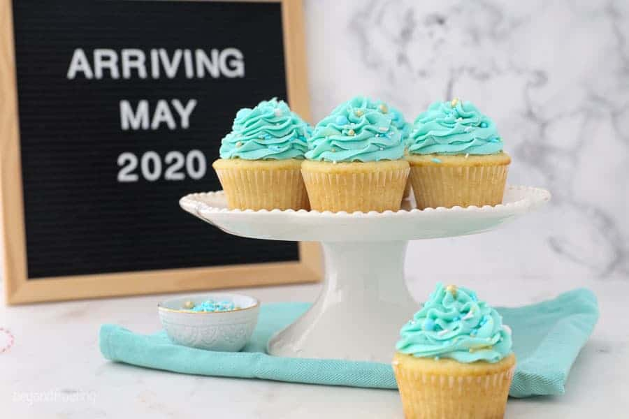 "A letter board that says ""arriving May 2020"" with some blue frosted cupcakes"