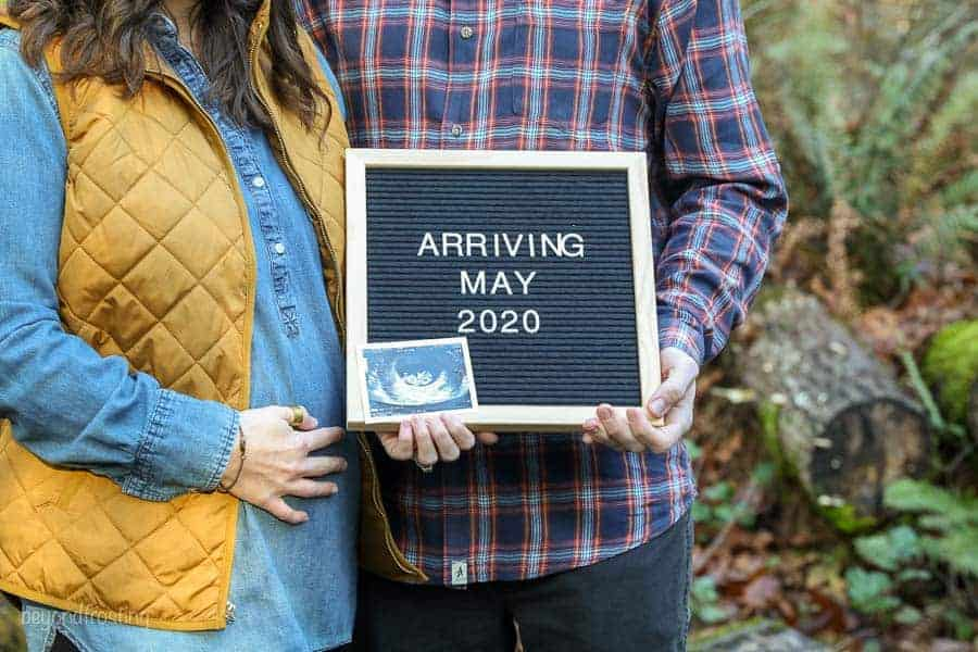 A baby announcement with the husband and wife holding a letter board that say Arriving May 2020