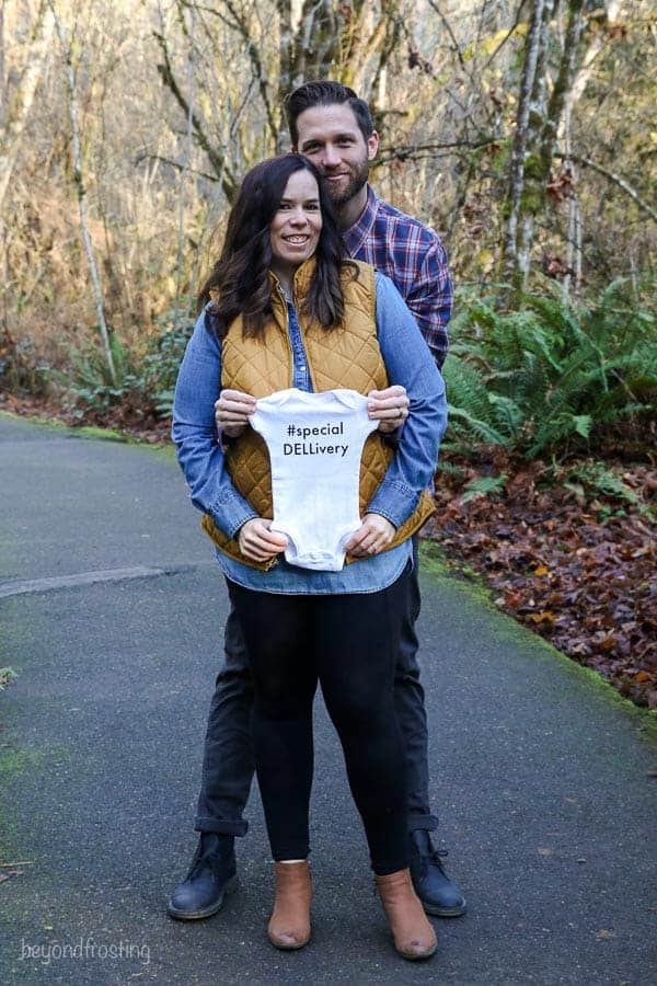"A baby announcement with the husband and wife holding a baby onesize that says ""specialDELLivery"""