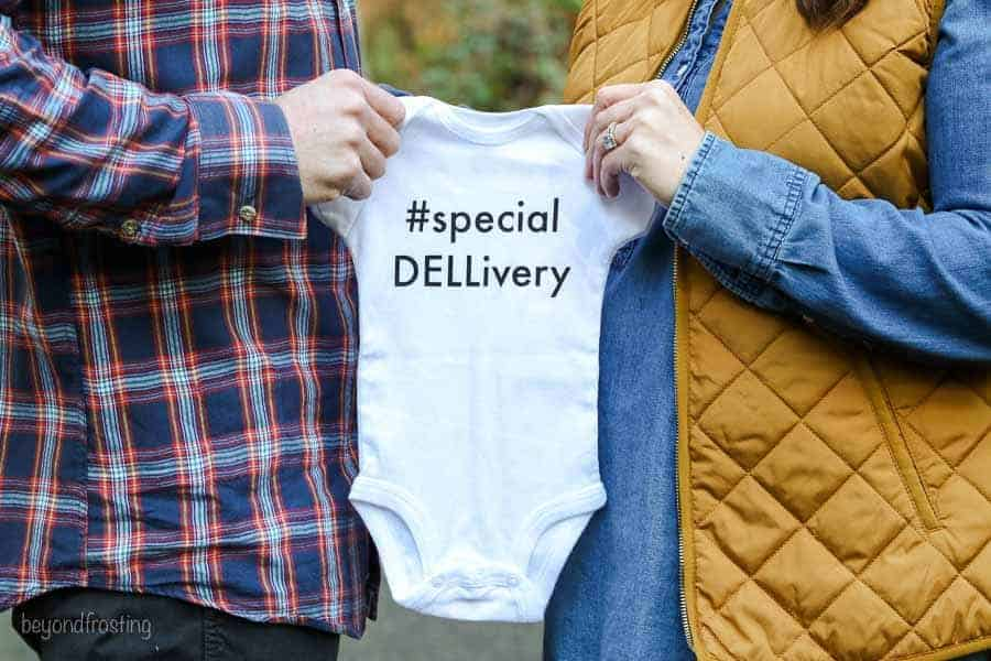 A baby announcement with the husband and wife holding an a baby onesie that says #specialDELLivery