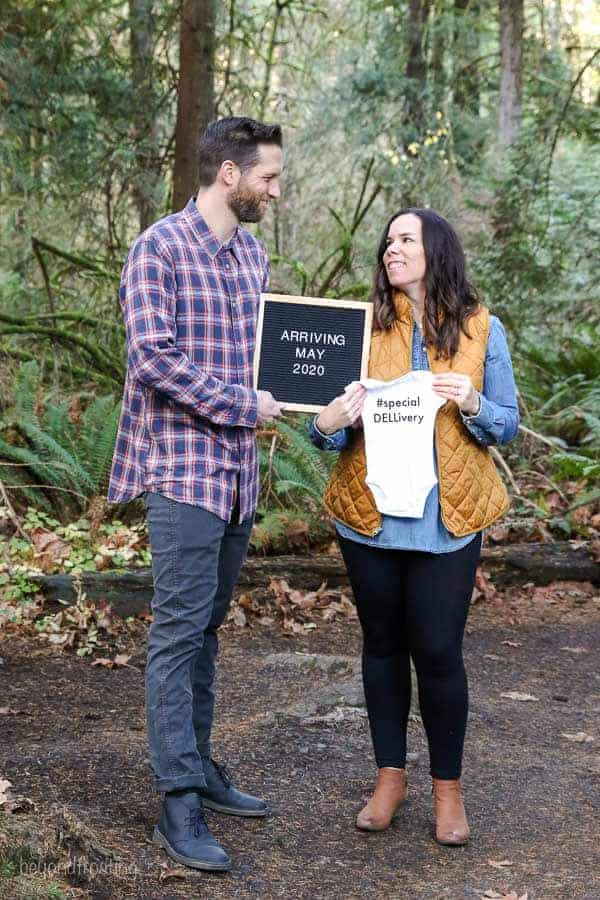 A baby announcement with the husband and wife holding a letterboard and a onesie
