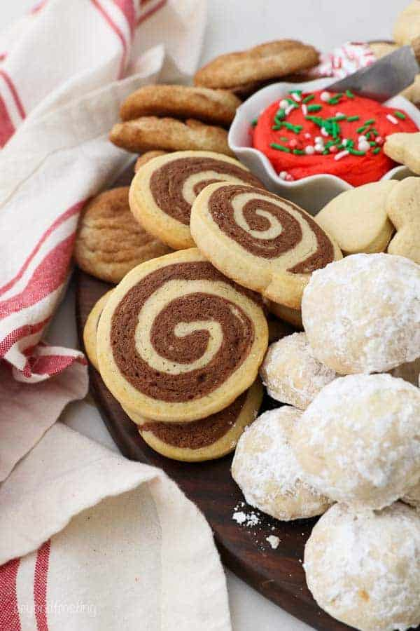 A close up of a dessert charcuterie board showing both pinwheel and snowball cookies