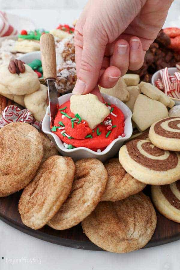 A mini sugar cookie being dipped in some red colored buttercream