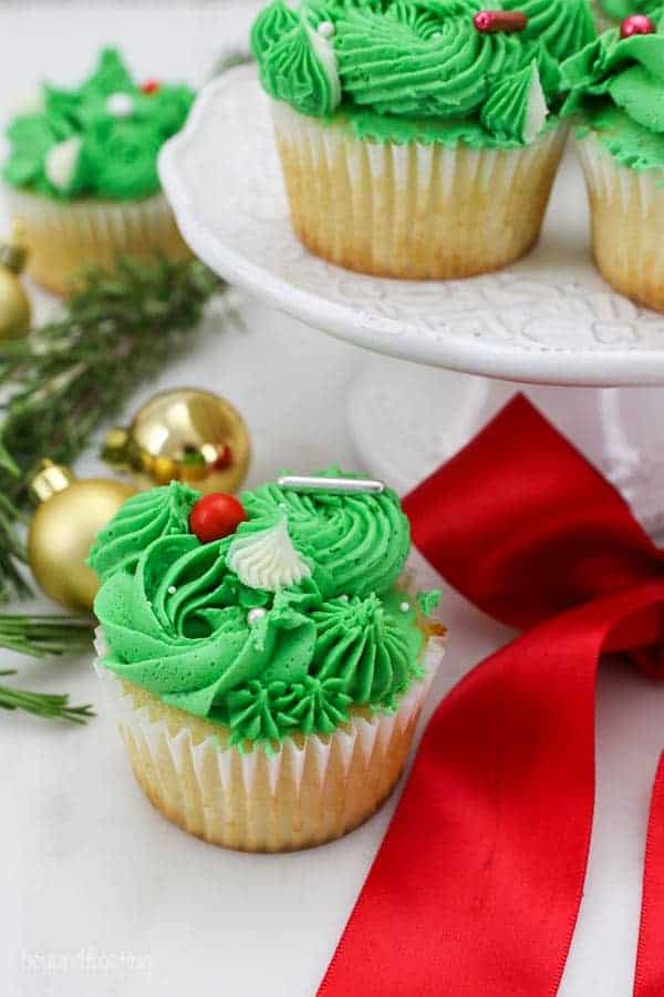 Gorgeous frosted green cupcakes with a red ribbon, gold Christmas bulbs and a white cake stand